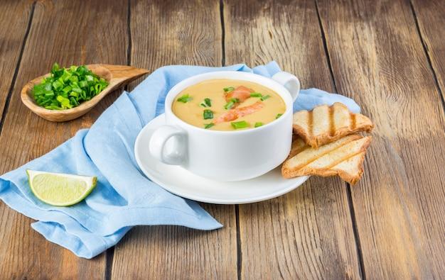 Zuppa di crema con salmone e cipolla verde servita con toast croccanti. copia spazio Foto Premium