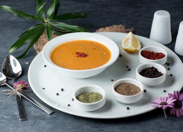 Zuppa di lenticchie servita con limone, sumac, palline di pepe nero e menta secca Foto Gratuite