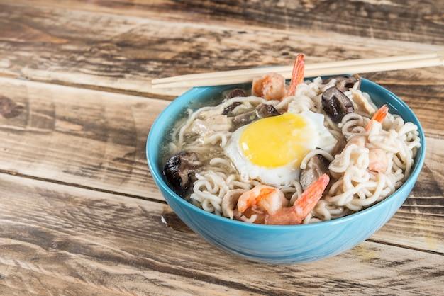 Zuppa di noodles istantanei con gamberi, uova e funghi. Foto Premium