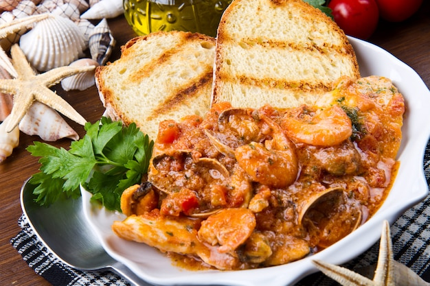 Zuppa di pesce con btread alla griglia sul vaso di coccio Foto Premium