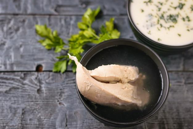 Zuppa di petto di pollo bollito e crema di cavolfiore su un tavolo di legno nero. Foto Premium
