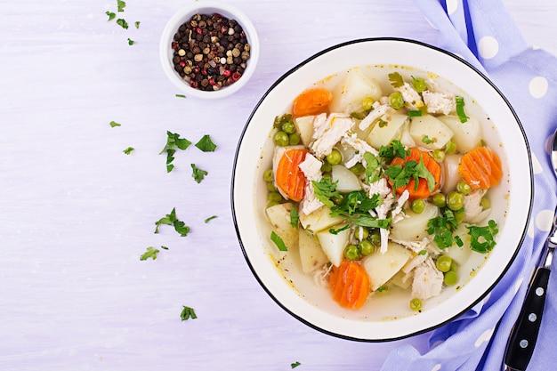 Zuppa di pollo con piselli, carote e patate in una ciotola bianca su una luce, vista dall'alto Foto Premium