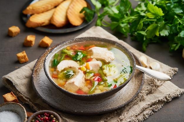 Zuppa di pollo fatta in casa con verdure, crostini, broccoli su testa di moro Foto Premium