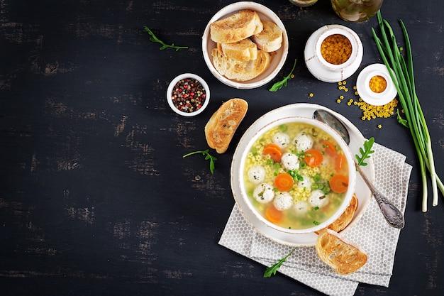 Zuppa di polpette italiane e pasta stellare in ciotola sul tavolo nero. Foto Premium