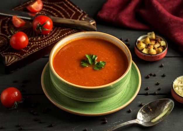 Zuppa di pomodoro con verde sul tavolo Foto Gratuite