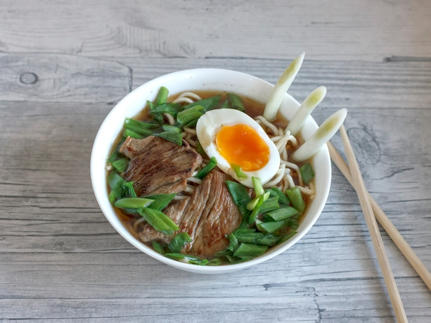 Zuppa di ramen con cipolle fresche, uova sode e carne fritta Foto Premium