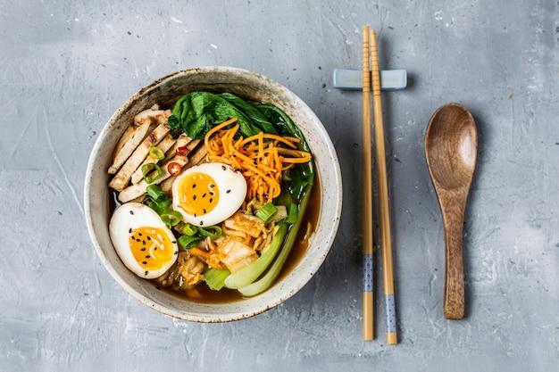 Zuppa di ramen in stile asiatico con cavolo cinese, carota, lime, semi di sesamo, pollo e uova Foto Premium