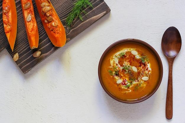 Zuppa di zucca e carote arrosto con crema, pepe nero e semi di zucca, tagliere e fette di zucca fresche, pane nero Foto Gratuite