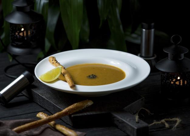 Zuppa di zucca in brodo di pollo con bastoncini di cannella e fette di limone Foto Gratuite