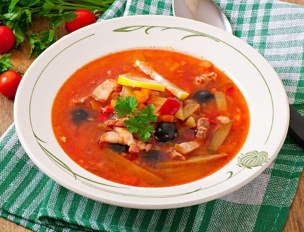 Zuppa solyanka russa con carne, olive e cetriolini in ciotola di legno Foto Premium