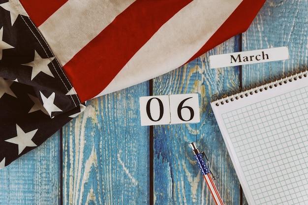 06 de março dia do calendário bandeira dos estados unidos da américa símbolo da liberdade e da democracia com o bloco de notas em branco e caneta na mesa de escritório de madeira Foto Premium