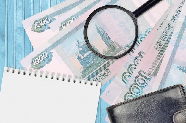 1000 notas de rublos russos e lupa com bolsa preta e bloco de notas. conceito de dinheiro falso. procure diferenças em detalhes em notas de dinheiro para detectar dinheiro falso Foto Premium