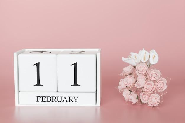 11 de fevereiro. dia 11 do mês. calendar o cubo no fundo cor-de-rosa moderno, no conceito do negócio e em um evento importante. Foto Premium