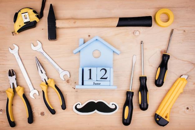 12 de junho - dia dos pais. conceito masculino. ferramentas de reparo - martelo, chaves de fenda, chaves ajustáveis, alicates. folha de papel branco. Foto Premium