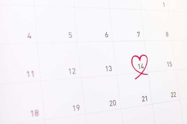 14 de fevereiro com coração rosa no calendário Foto Premium