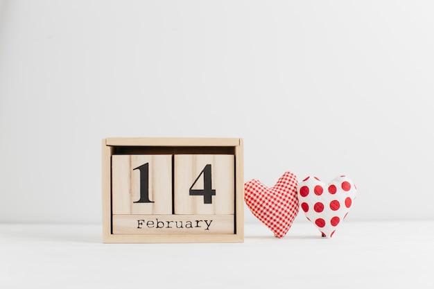 14 ebruary no calendário de madeira perto de corações artesanais Foto gratuita