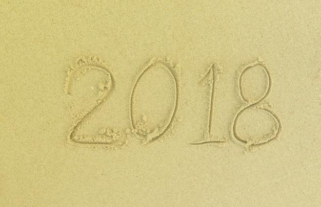 2018 escreva na areia na praia no dia. feliz ano velho. Foto Premium