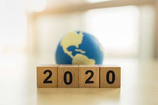 2020 ano novo, conceito global e de negócios. feche acima da pilha de bloco numérico de madeira e bola de brinquedo mini mundo com espaço de cópia Foto Premium