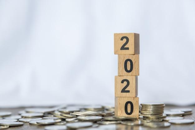 2020 ano novo, dinheiro e conceito de negócio. close-up da pilha de brinquedo de bloco de madeira de número na pilha de moedas Foto Premium
