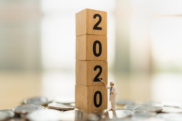 2020 ano novo, negócios, economia e conceito de planejamento. close-up da figura em miniatura de trabalhador em pé e pintura na pilha de brinquedo de madeira do bloco de número na pilha de moedas com espaço de cópia Foto Premium