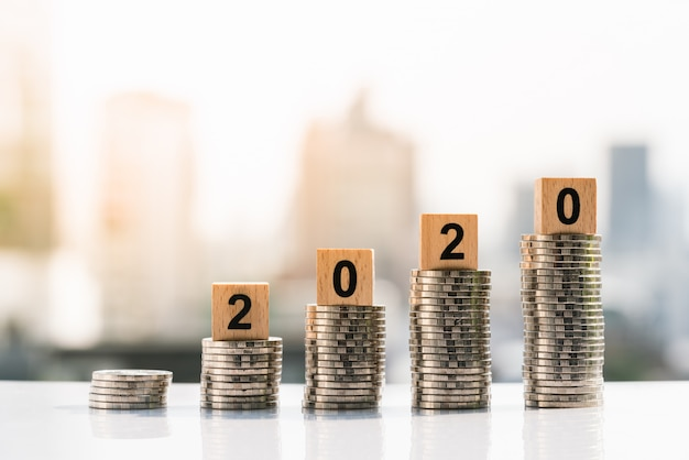 2020 blocos de madeira em cima da pilha de moedas em fundos da cidade. Foto Premium