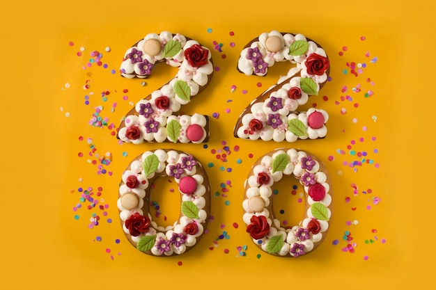 2020 bolos e ornamentos na superfície amarela Foto Premium