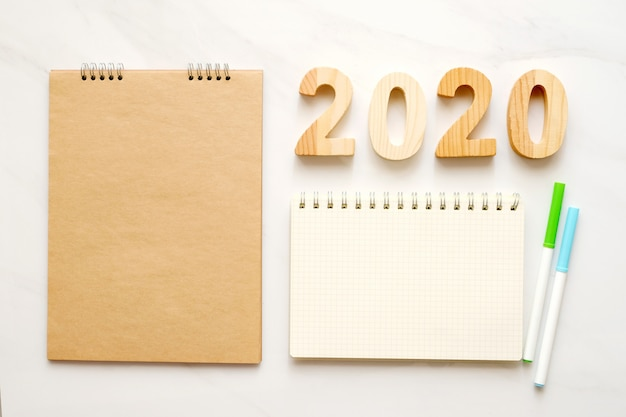 2020 letras de madeira e papel de caderno em branco sobre fundo de mesa de mármore branco Foto Premium