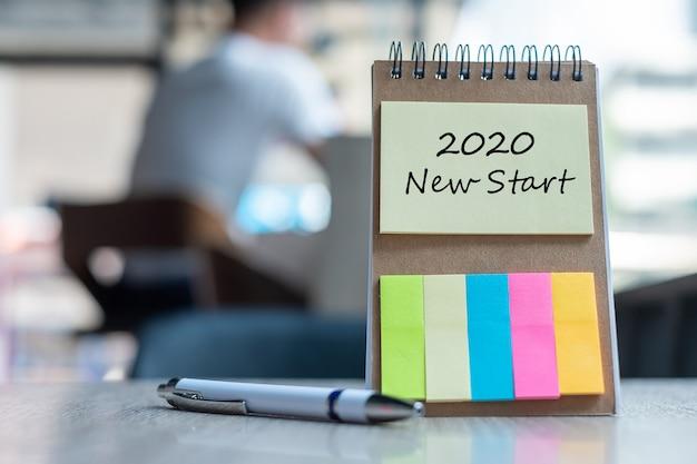 2020 new start palavra no papel de nota com a caneta na mesa de madeira Foto Premium