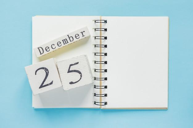 25 de dezembro em um calendário de madeira em um livro. conceito de natal e ano novo Foto Premium