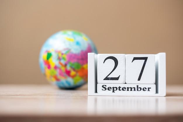 27 de setembro do calendário de madeira na mesa, conceito de dia de turismo de palavra Foto Premium