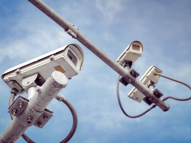 3 câmeras de segurança cctv em um poste alto para proteção pública. Foto Premium