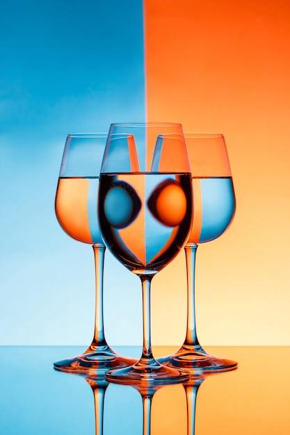 3 copo de vinho com água sobre a parede azul e laranja Foto gratuita