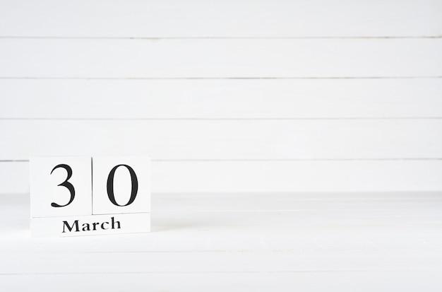 30 de março, dia 30 do mês, aniversário, aniversário, calendário de bloco de madeira sobre fundo branco de madeira com espaço de cópia para o texto. Foto Premium