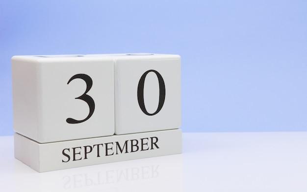 30 de setembro dia 30 do mês, o calendário diário na mesa branca com reflexão Foto Premium