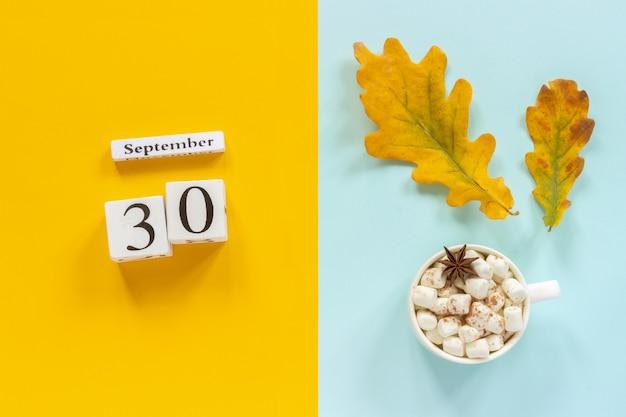 30 de setembro, xícara de chocolate com marshmallows e folhas de outono amarelas sobre fundo azul amarelo. Foto Premium