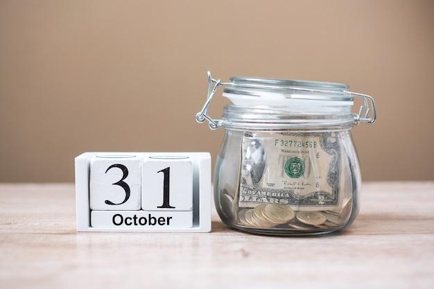 31 de outubro de calendário de madeira e dinheiro em frasco de vidro na mesa, dia mundial da economia Foto Premium
