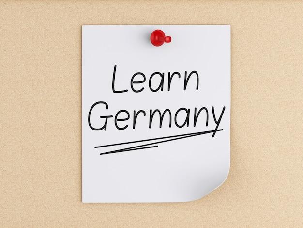 3d aprenda alemanha, palavra no post-it sobre a cortiça. Foto Premium