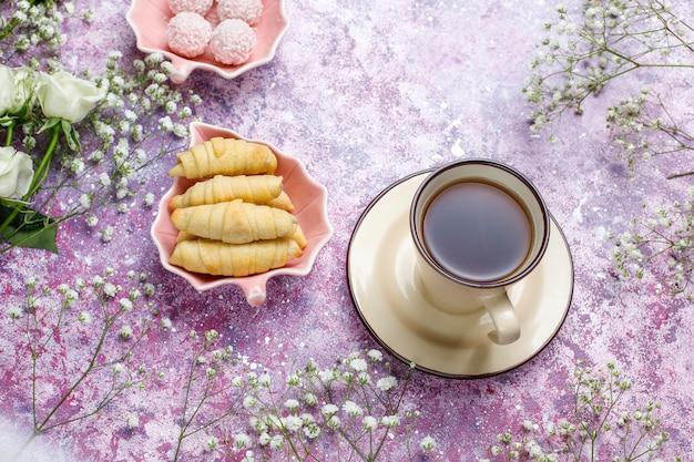 8 de março - cartão do dia da mulher com flores brancas, doces e uma xícara de chá Foto gratuita