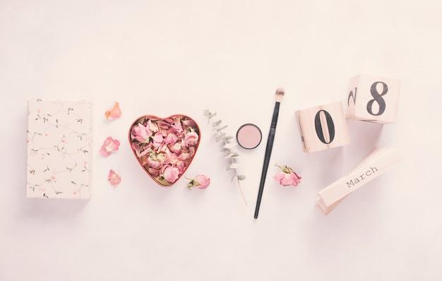 8 de março de inscrição com pétalas de rosa e pincel na mesa Foto gratuita