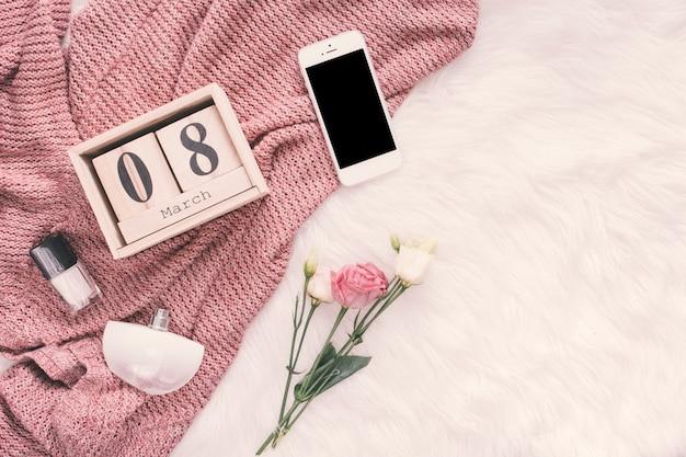 8 de março inscrição com smartphone e rosas no cobertor Foto gratuita
