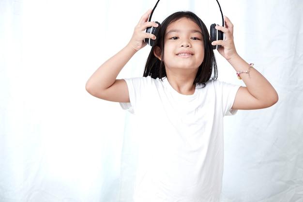 8s menina com fones de ouvido Foto Premium