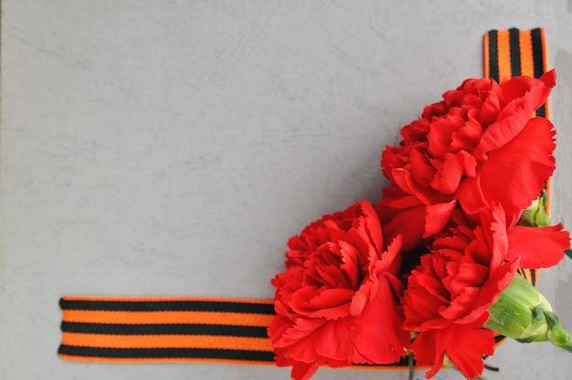9 de maio cartão do dia da vitória. cravos vermelhos e fita de st george no fundo de um velho álbum de fotos. Foto Premium