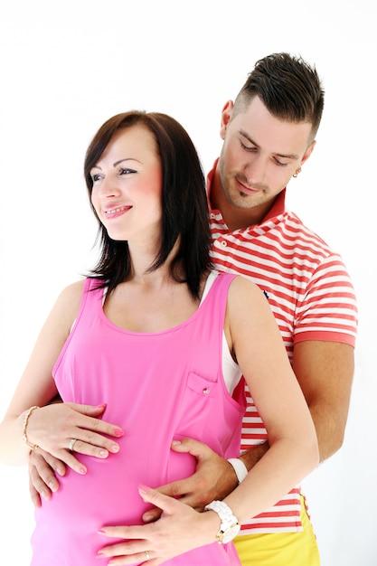 Gestante e seu companheiro abraçando a barriga da mulher