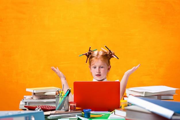 A adolescente ruiva com muitos livros em casa. foto de estúdio Foto gratuita