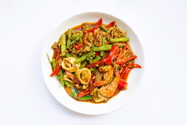 A agitação picante fritou o shimp, o calamar e a carne de porco com pasta do sul tailandesa do pimentão e longbean no fundo branco. Foto Premium