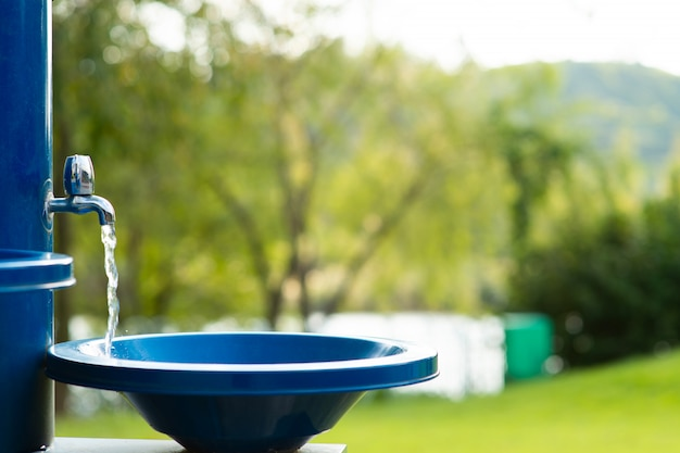 A água está correndo no parque na torneira azul Foto Premium
