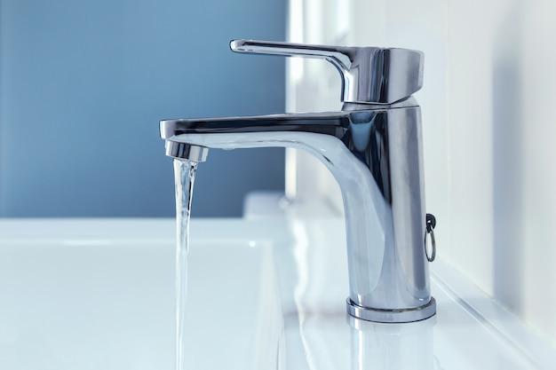 A água flui de uma torneira cromada brilhante para a pia. Foto Premium