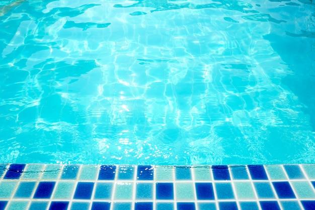 A água ondulou na superfície da água da piscina para o fundo Foto Premium