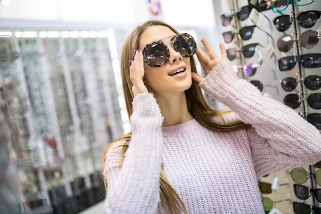 A aluna está se preparando para estudar e experimente novos óculos para seu visual perfeito em uma loja profissional Foto gratuita