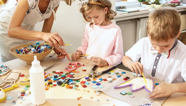 A arte do puzzle em mosaico para crianças, um jogo criativo para crianças. as mãos estão jogando mosaico na mesa. detalhes coloridos multicoloridos close-up. criatividade, desenvolvimento infantil e conceito de aprendizagem Foto gratuita